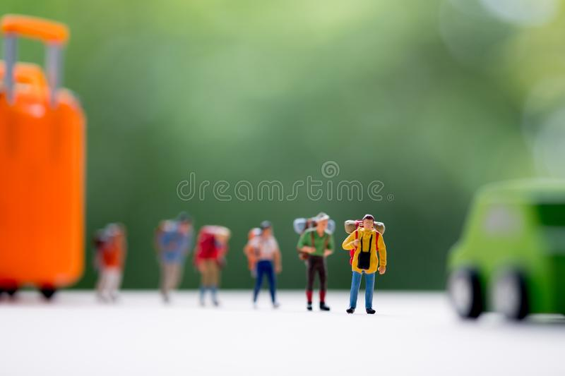 Miniature people : Group of traveler standing on road for hopping find passing car carrying to transfer royalty free stock photos