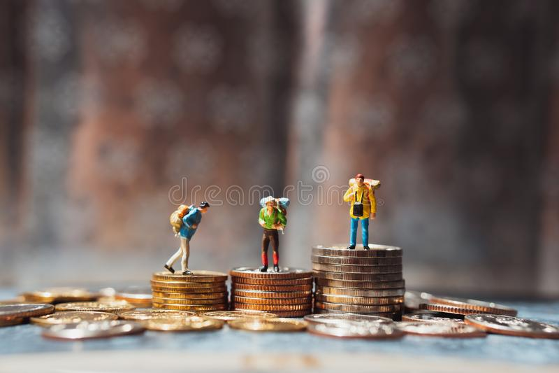 Miniature people, group of travelers standing on stack coins using as business competition and financial concept stock image