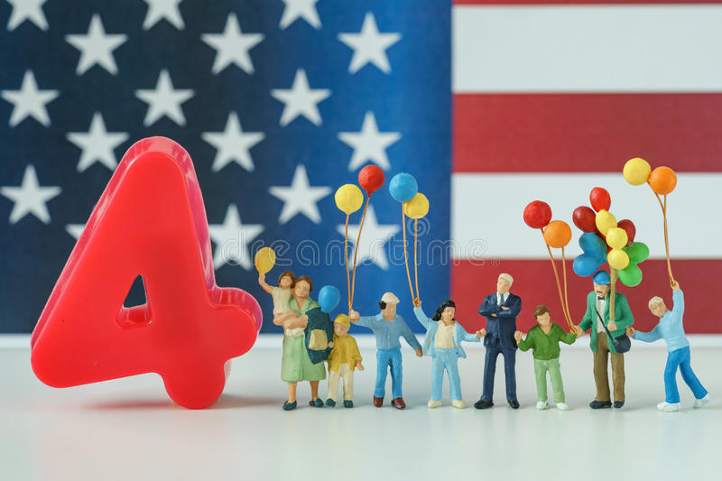 miniature people, happy american family holding balloon with number 4 and United State national flag in the background as stock photography