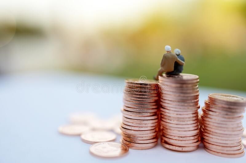 Miniature people: Happy old people sitting on coins stack, Retirement  and Life insurance Concept. Miniature people: Happy old people sitting on coins stack royalty free stock photography