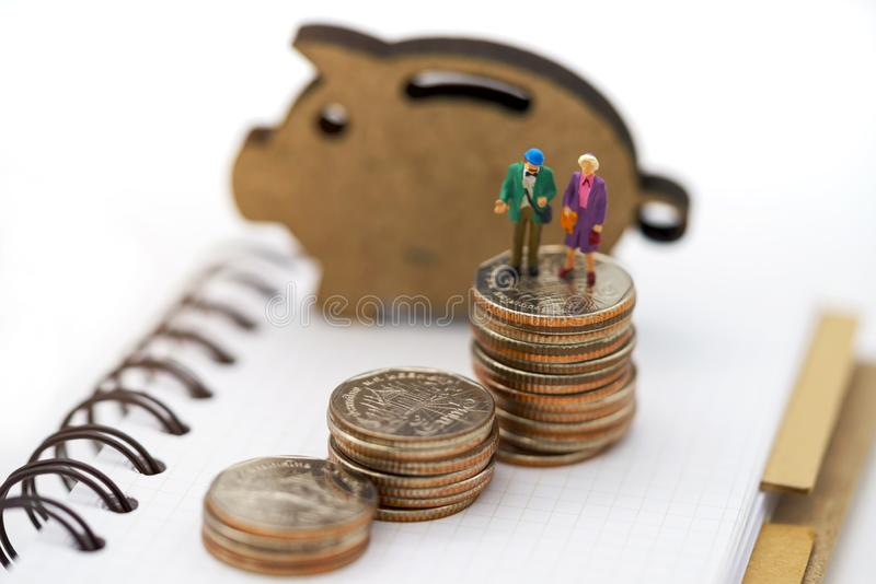 Miniature people: Happy old people standing on coins stack, Retirement planning, Emergency plan, Life insurance and Financial royalty free stock photo