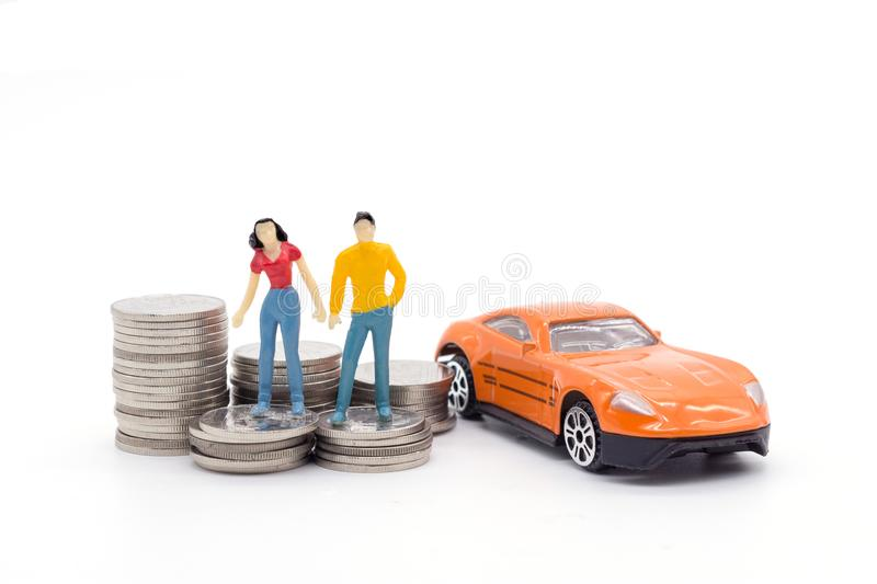 Miniature people,husband and wife standing with car and stack co stock image
