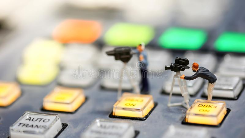 Miniature people : journalists , cameraman ,Videographer at work stock photo