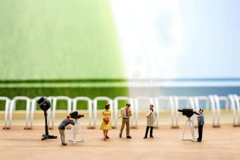 Miniature people : journalists , cameraman ,Videographer at work. Shooting of the people,using for concept of TV talk Show Host Day royalty free stock photo