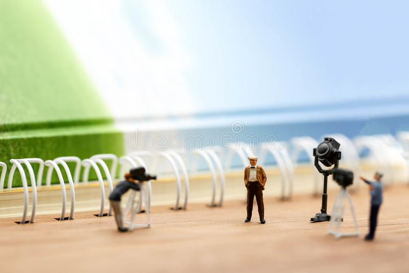 Miniature people : journalists , cameraman ,Videographer at work. Shooting of the people,using for concept of TV talk Show Host Day stock images