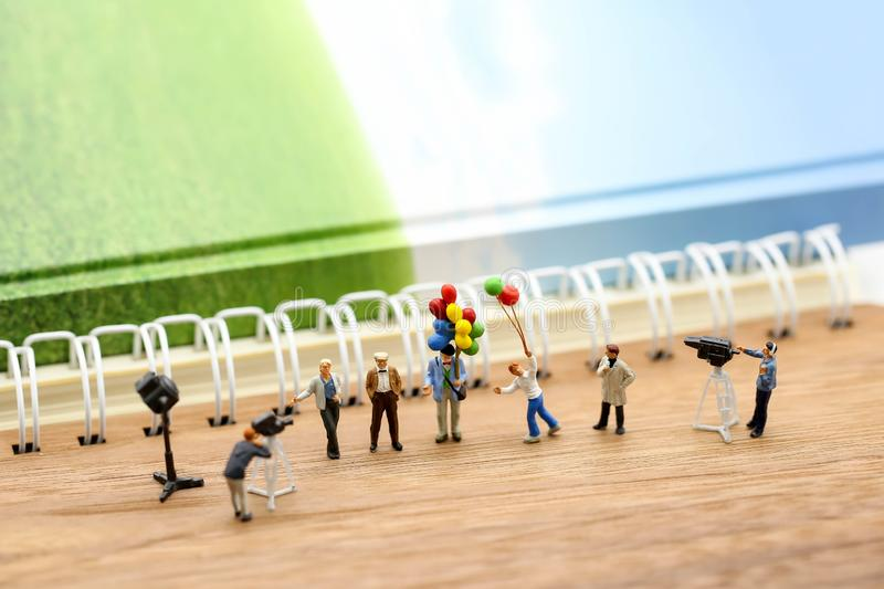 Miniature people : journalists , cameraman ,Videographer at work. Shooting of the people,using for concept of TV talk Show Host Day stock photography
