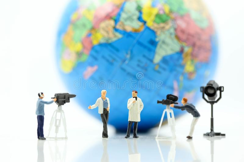 Miniature people : journalists , cameraman ,Videographer at work. Shooting with world using for concept of World Television Day royalty free stock photos