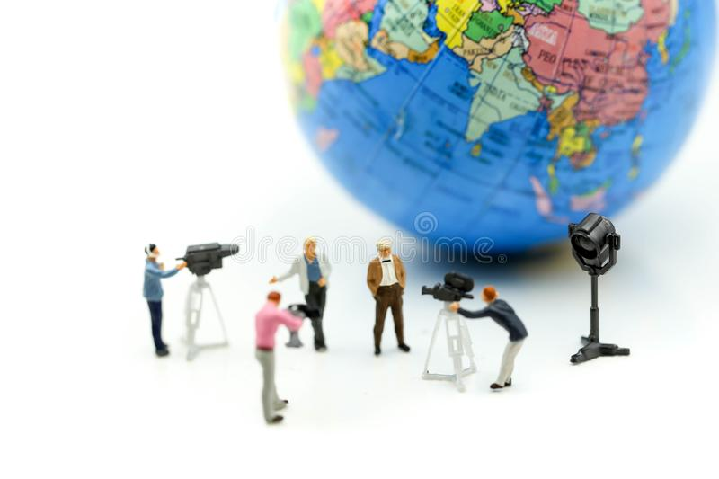 Miniature people : journalists , cameraman ,Videographer at work. Shooting with world using for concept of World Television Day stock photo