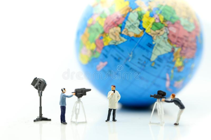 Miniature people : journalists , cameraman ,Videographer at work. Shooting with world using for concept of World Television Day royalty free stock image
