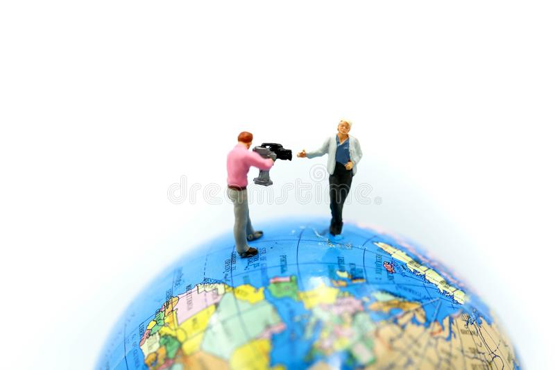 Miniature people : journalists , cameraman ,Videographer at work. Shooting with world using for concept of World Television Day royalty free stock photo