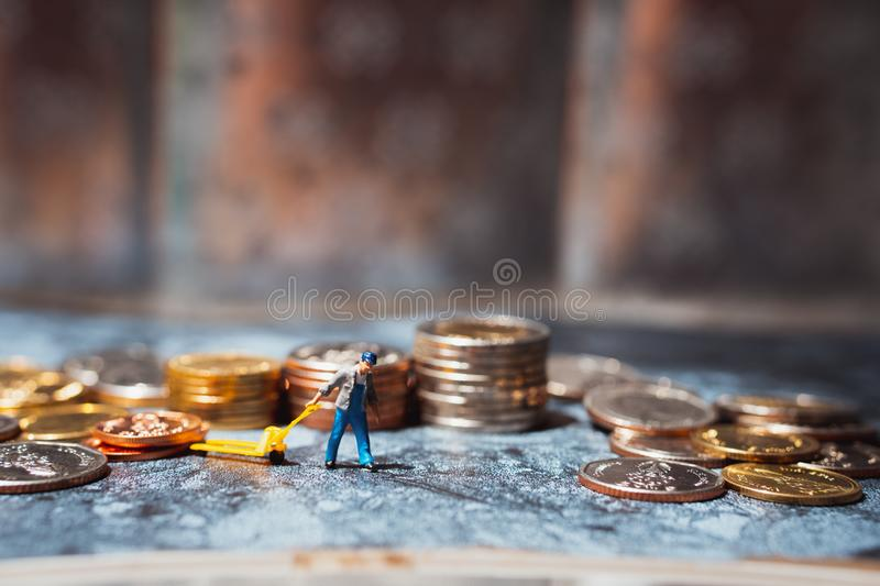 Miniature people, man pulling stack coins using for logistic, business and financial concept royalty free stock photography