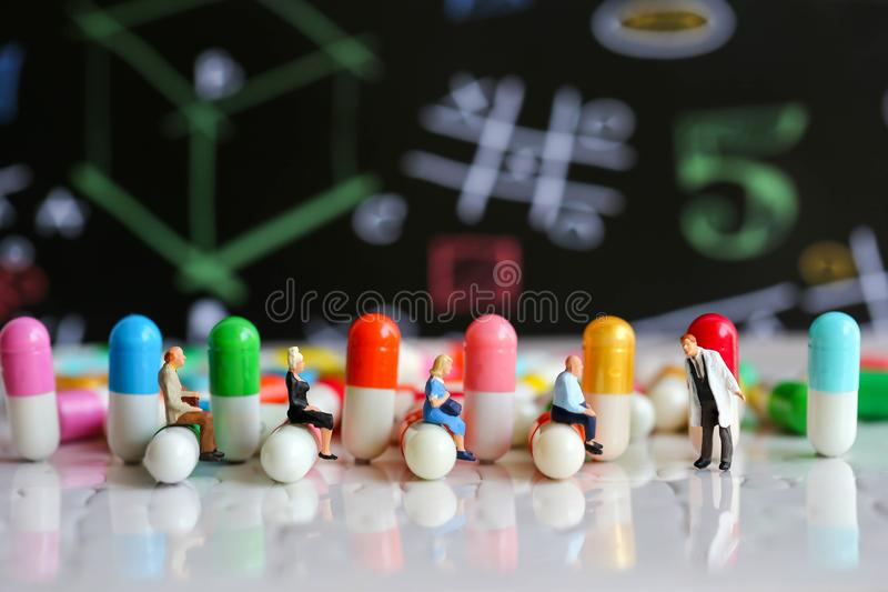 Miniature people : man working on capsule drug using for healthy stock photography