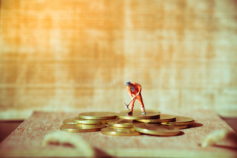 Miniature people, mechanic working on stack coins. Using for business and industry concept - Vintage filter royalty free stock photo