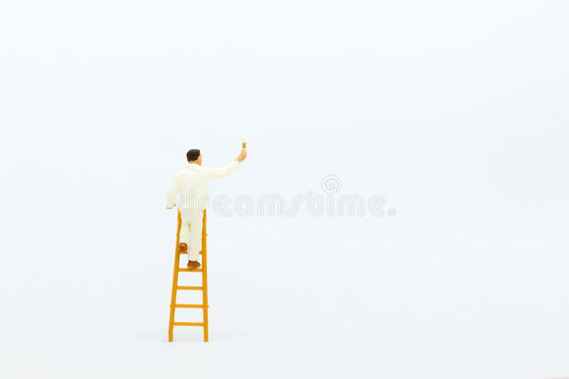 Miniature people: mini figure with ladder and white painting in front of a wall.  stock photo