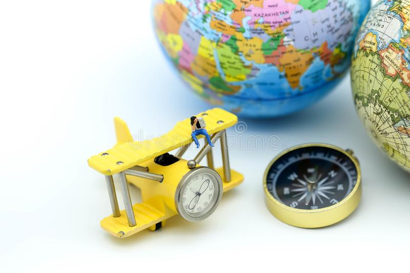 Miniature people : on paddle boat with Compass with world map an stock image