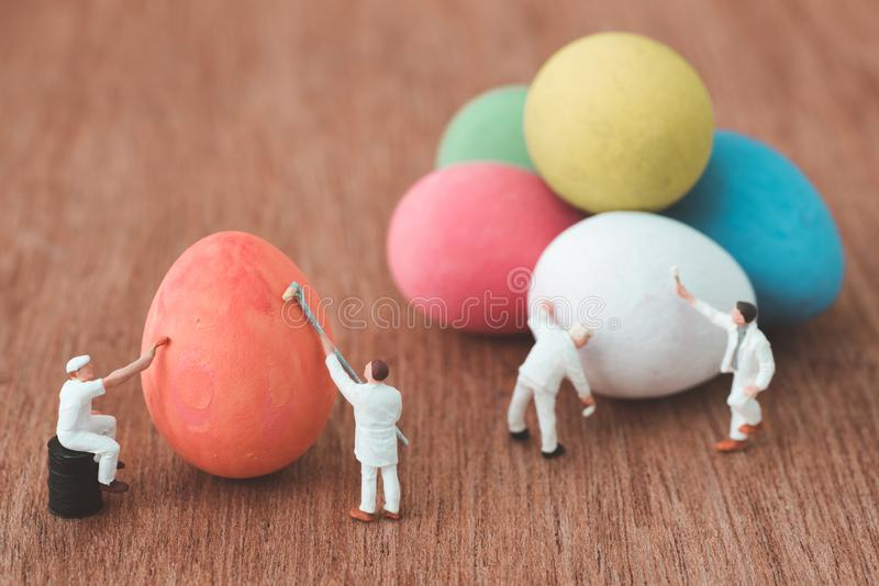 Miniature people painting easter eggs stock photo