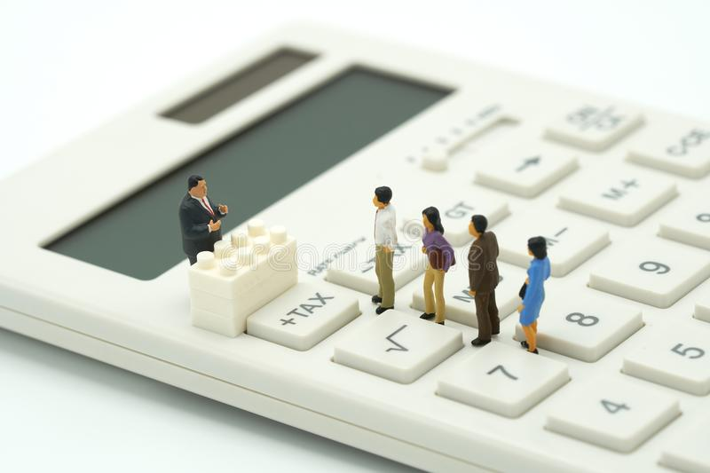 Miniature people Pay queue Annual income TAX for the year on calculator. using as background business concept and finance concep. T with copy space for your text royalty free stock photography