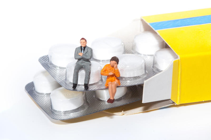 Miniature people - people posing in front of pills royalty free stock photography