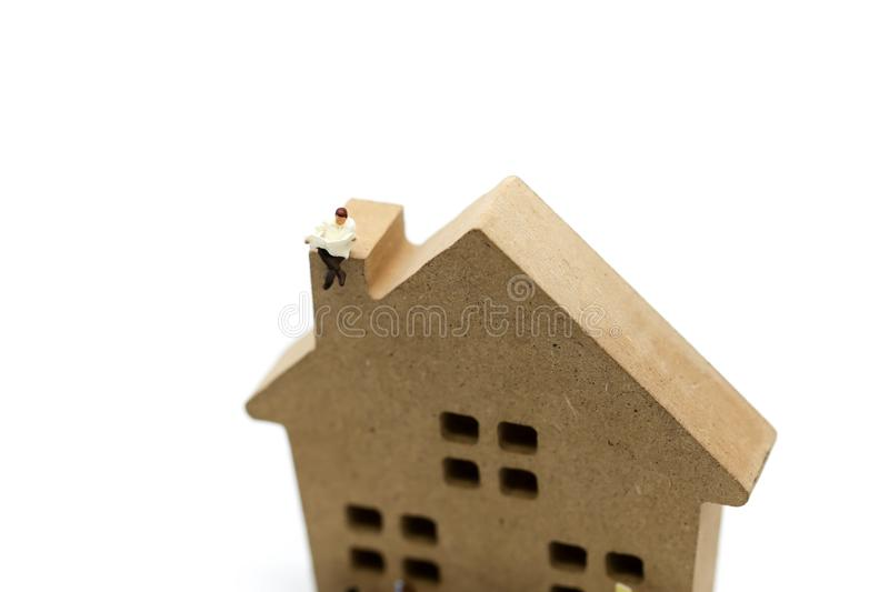 Miniature people : people reading a book with wooden house toy, stock photos