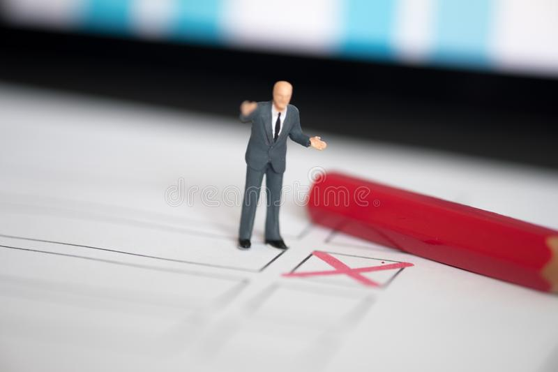 Miniature people of a politician standing on election ballot. With red pen. Election debates or press conference concept royalty free stock photography