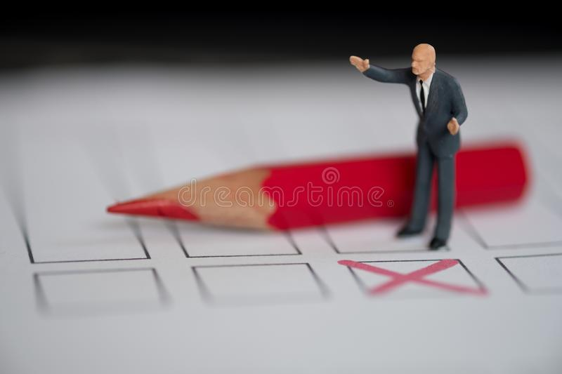 Miniature people of a politician standing on election ballot. With red pencil. Election debates or press conference concept royalty free stock photo