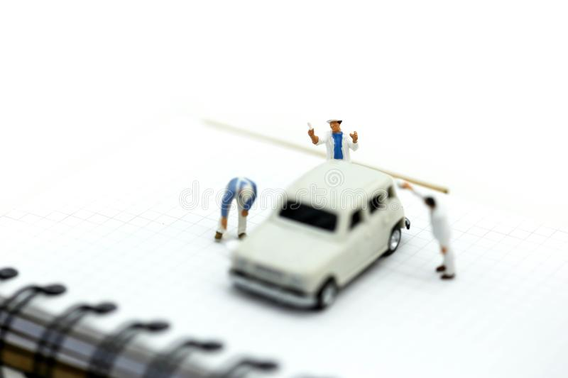 Miniature people : Professional painting car in a paint chamber royalty free stock photo