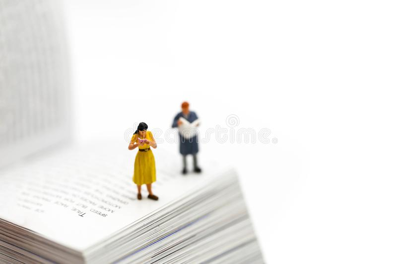 Miniature people : reading a book and Dictionary using for conce. Pt of Dictionary Day stock images