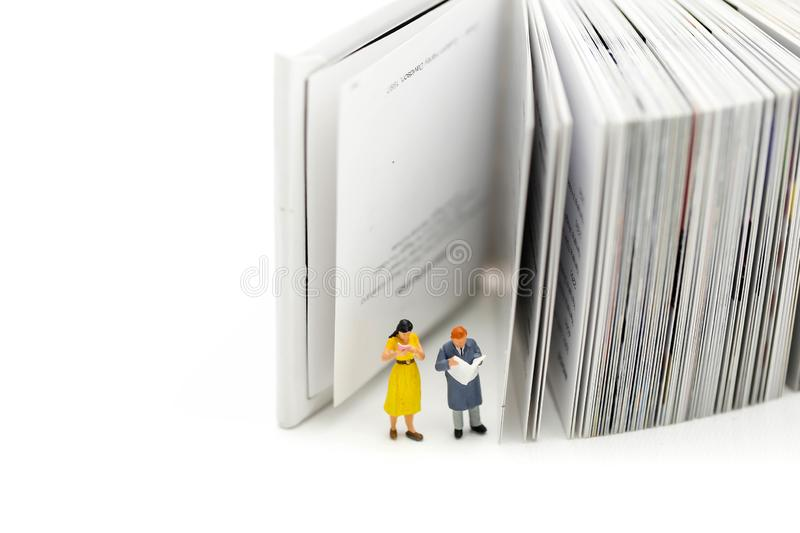Miniature people : reading a book and Dictionary using for concept of Dictionary Day. stock photography
