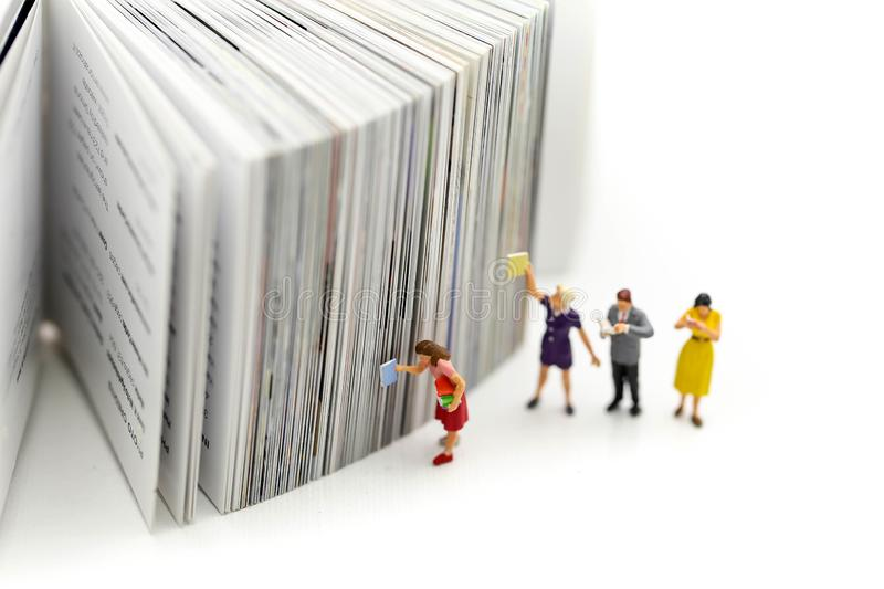 Miniature people : reading a book and Dictionary using for concept of Dictionary Day. royalty free stock image
