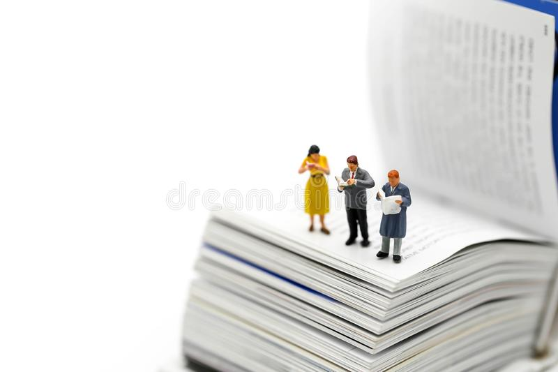 Miniature people : reading a book and Dictionary using for concept of Dictionary Day. royalty free stock photography
