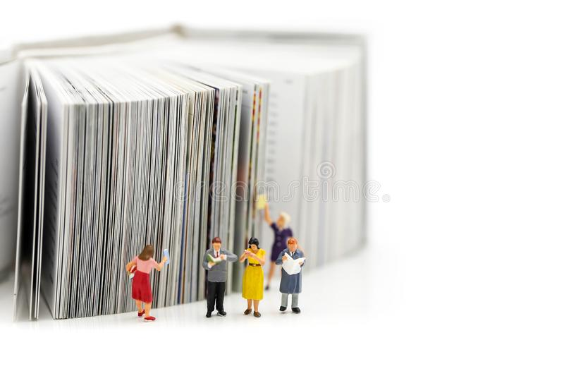Miniature people : reading a book and Dictionary using for concept of Dictionary Day. royalty free stock images