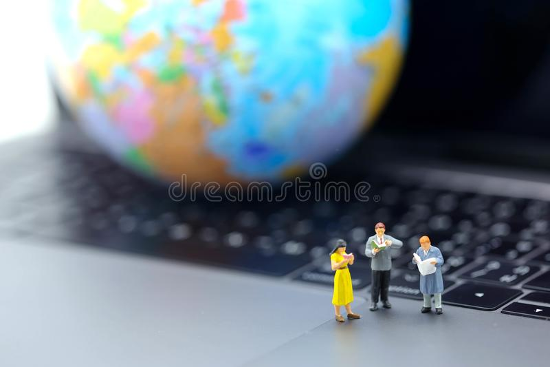 Miniature people : reading book on laptop with globe world map,. Education or business concept royalty free stock images
