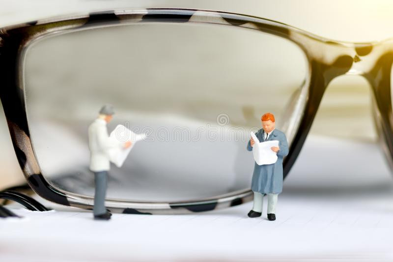 Miniature people reading and standing on book with glasses using as background, royalty free stock photography