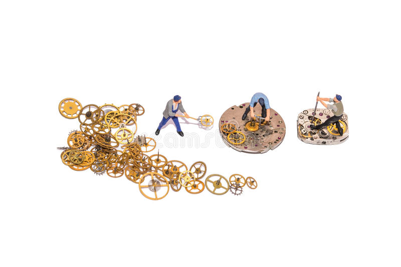 Miniature people repairing clockwork. Teamwork. Help in the work. Working employees. A pile of gear. Gears and clockwork isolated. Yellow cogs stock photo