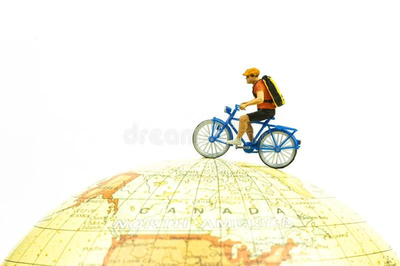Miniature people riding bicycle around the globe isolated on white background close up.Image concept stock photo