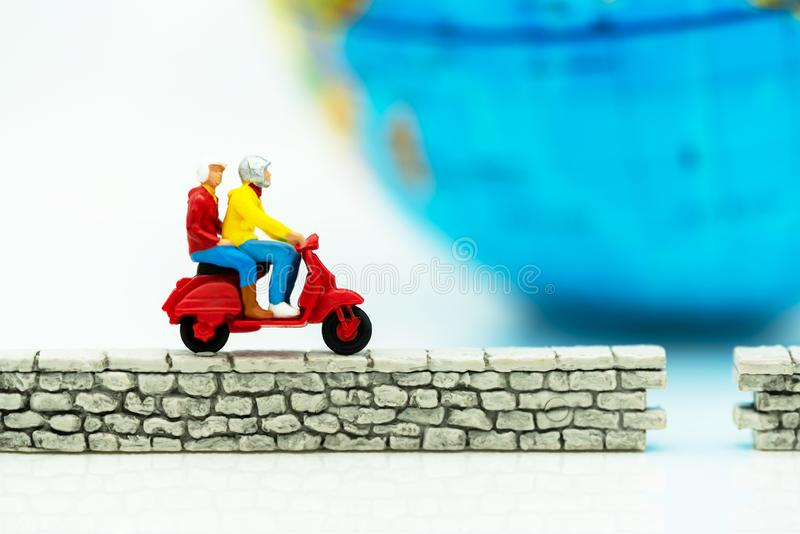 Miniature people riding bike on wall and world royalty free stock image