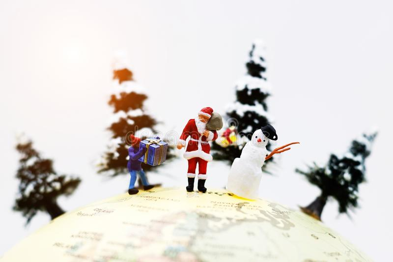 Miniature people: Santa Claus, kid and snowman with Christmas tree on globe. stock photography