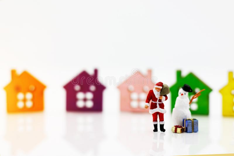 Miniature people: Santa Claus and snowman with gift standing before Wooden house model. Merry Christmas and Happy New Year concep stock photography