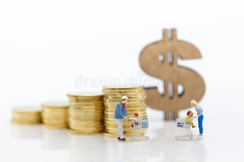 Miniature people : Shoppers with shopping cart , stack of coins. Image use for retail business concept royalty free stock photo