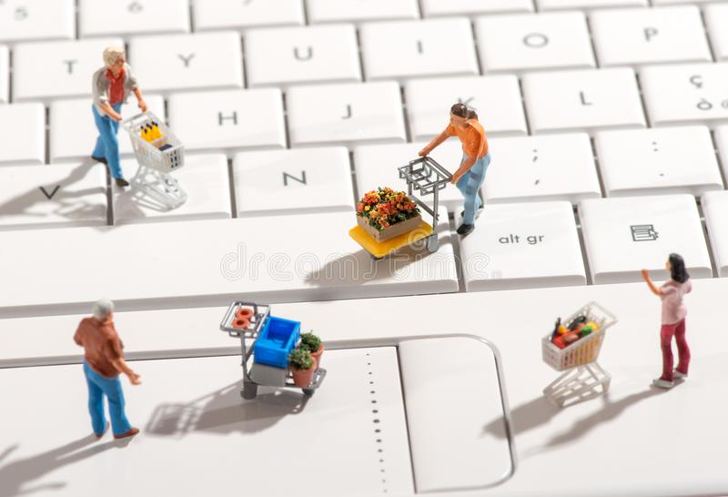 Miniature people with shopping carts on a keyboard royalty free stock images