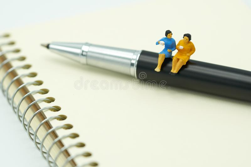 Miniature people Sit on the pens, exchange ideas, discuss problems using as background business concept and finance concept with c. Opy space for your text or royalty free stock photos