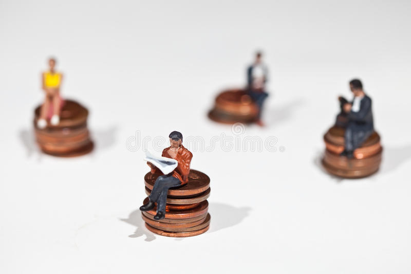 Miniature people sitting on coins stock photography