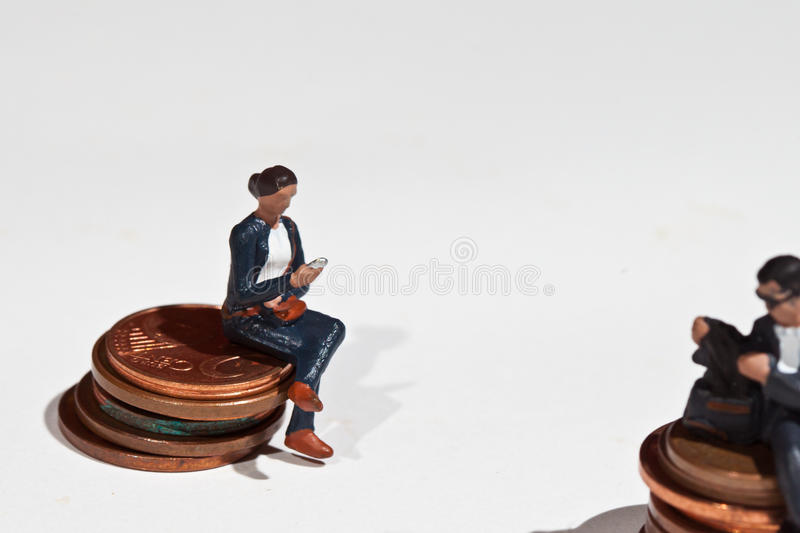 Miniature people sitting on coins royalty free stock photo