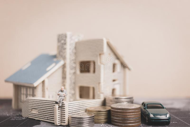 Miniature people sitting with coins money with home. Investment and growth in business concept royalty free stock images