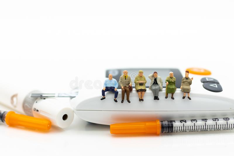 Miniature people sitting on glucose meter with lancet. Image use stock photo