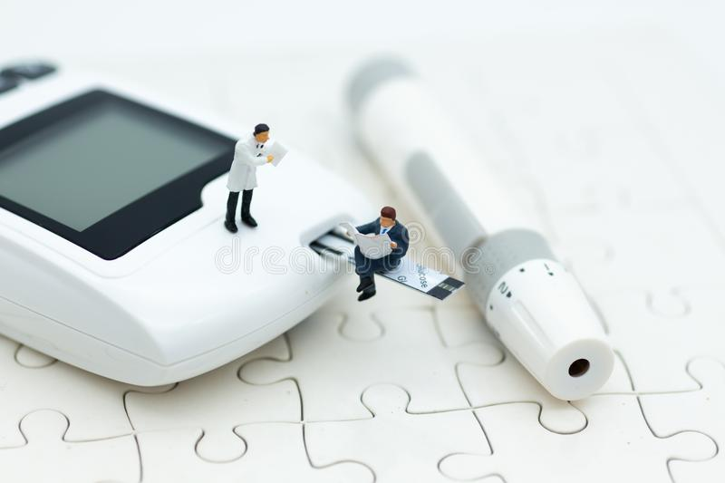 Miniature people sitting on glucose meter with lancet. Image use for medicine, diabetes, health care concept royalty free stock image