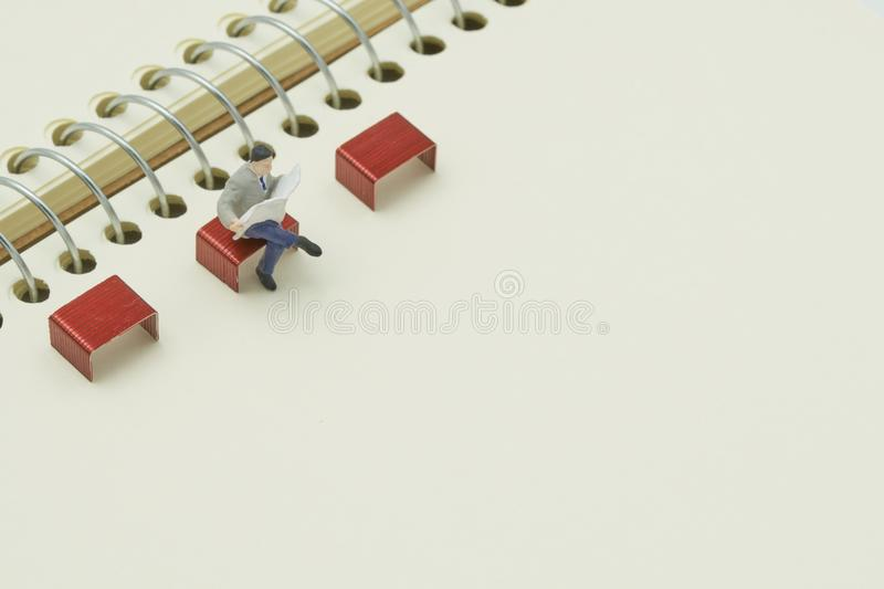 Miniature people sitting on red staples placed on a notebook. as background business concept with copy spaces. For your text or design stock photos