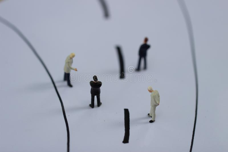 Miniature people: Small businessman figures walking on the street. stock photography