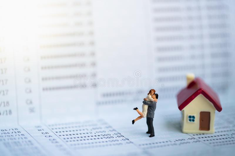 Miniature people: Small couple figures in love standing on bank passbook. Love and Valentine`s day concepts. family finance royalty free stock photos
