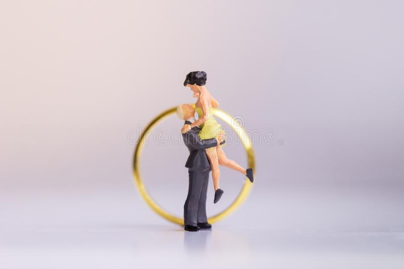 Miniature people: Small couple figures in love standing on white background. royalty free stock image